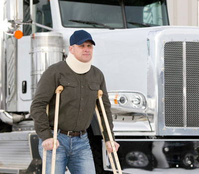 Man with neckbrace and crutches pictured in front of the cab of a white semi truck