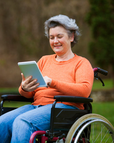 woman in wheelchair holding and looking at tablet computer